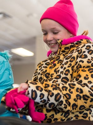 Darla Dallet tries on a pair of gloves during the ninth annual 'Coats for Kids' holiday program hosted by the New Jersey Motorsports Park Green Flag Children's Charities at the New Jersey Motorsports Park in Millville on Friday, December 2.