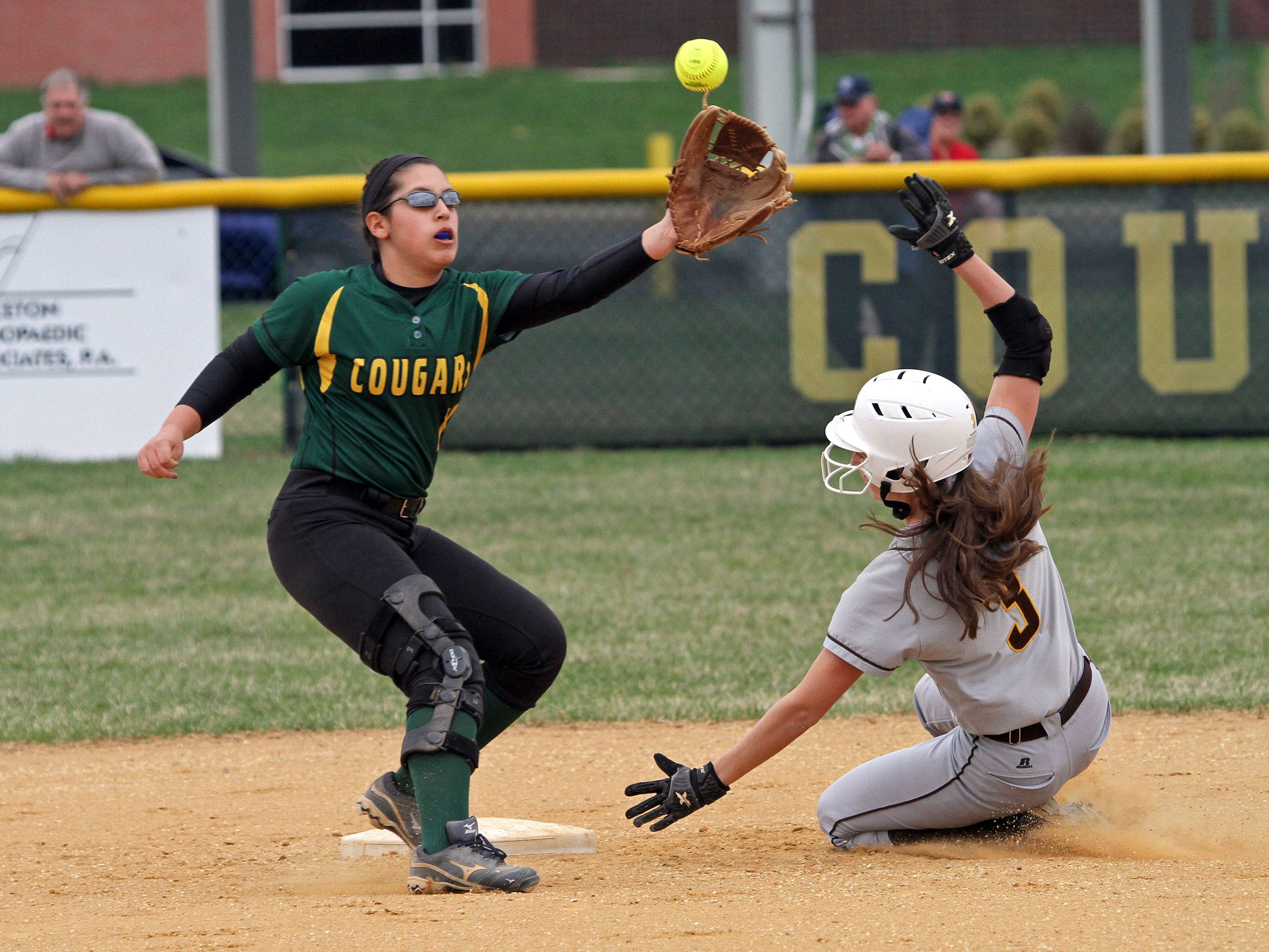 Watchung Hills' Kayla Schinik is safe stealing second as Montgomery's Kira Ferraiolo takes the throw. This is action of Watchung Hills at Montgomery in girls softball.
