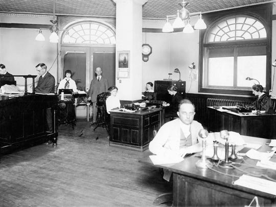 A worker at Newell & Truesdell with two telephones