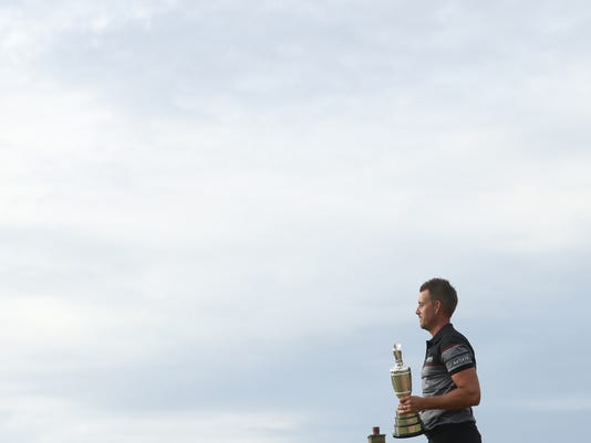 Henrik Stenson of Sweden walk round the 18th green with the the trophy after winning the British Open Golf Championships at the Royal Troon Golf Club in Troon, Scotland, Sunday, July 17, 2016. (AP Photo/Peter Morrison)