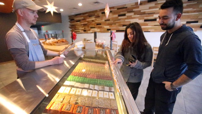 Retail clerk Aniel Gourley, left, attends Alejandro Rodriguez, right, and his girlfriend Adhylene De Leon at the new Belle Sucre Eastside location at 1830 Joe Battle Friday. The location opened Nov. 21. De Leon said she likes the Macaron pastries, which account for 30 percent of the bakery's sales, Gourley said.