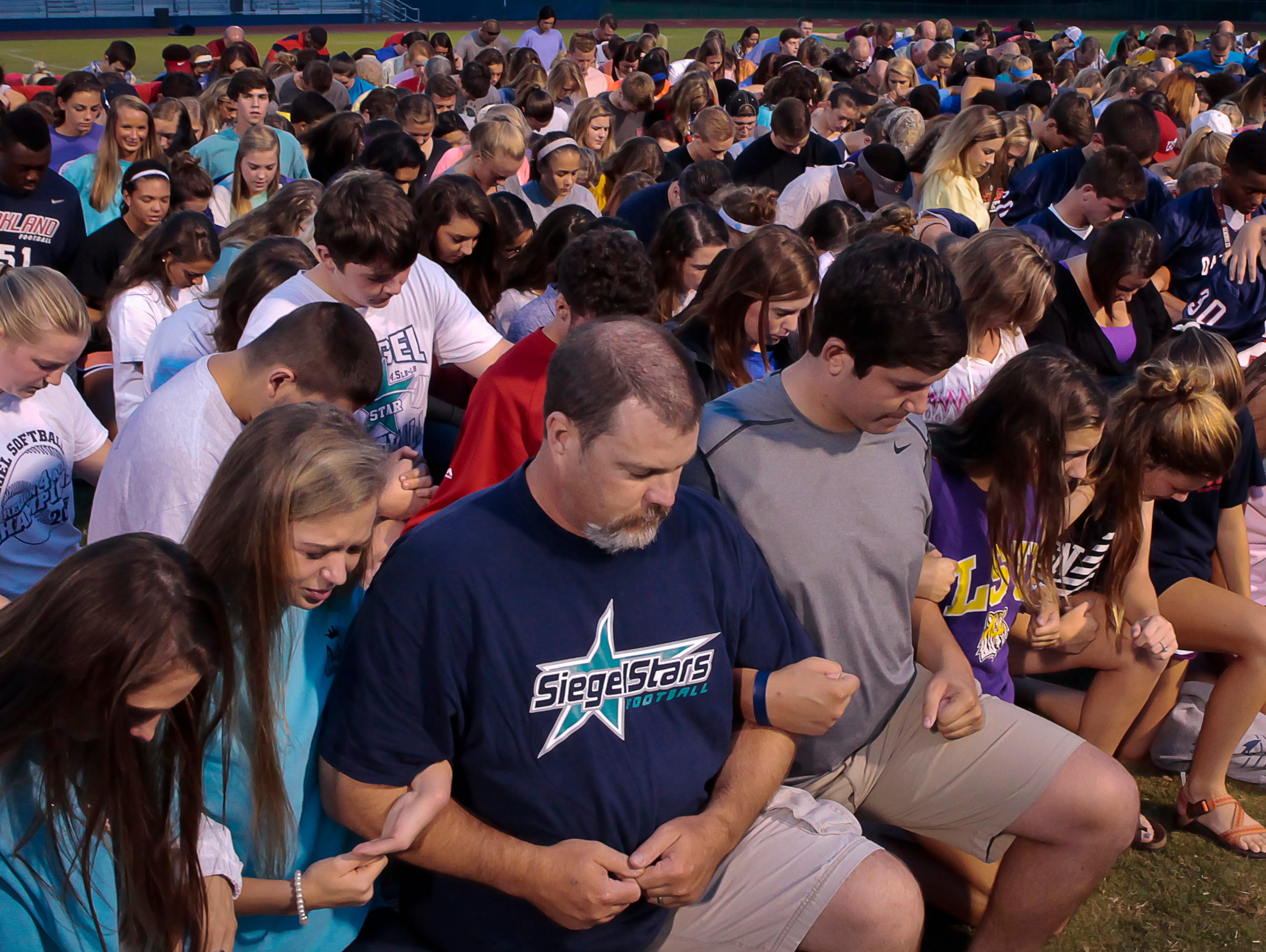 Siegel coaches, friends and teammates pray for sophomore Mason Loupe, who sustained a gunshot wound to the head on Saturday night.