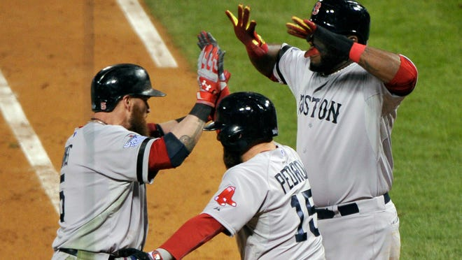 Boston Red Sox left fielder Jonny Gomes celebrates his three-run home run Oct. 27 with Dustin Pedroia and David Ortiz.