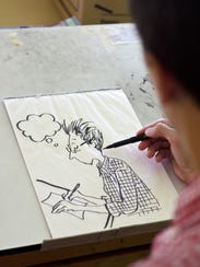 Cartoonist Alison Bechdel draws herself in her studio
