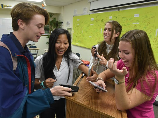 "Eleventh-grade students (from left) Conor O'Haire, 17, Tea Tee, 17, Mary Cate Stiles, 17, and Maura Ramsey, 16, reunite with their mobile phones on Wednesday March 22, after being without them for a week as part of a class project under teacher Louise Kennedy at St. Edward's School in Vero Beach. ""It's a lot of different emotions, at first I didn't really want it back but I've been looking forward to this all day,"" Ramsey said, ""Now that I have it back I'm pretty excited."" Fifty-five students participated in the project. ""It's nice to have the separation for the time that we had it but I'm really happy to be able to communicate with my family members and peers once again,"" Conor said."