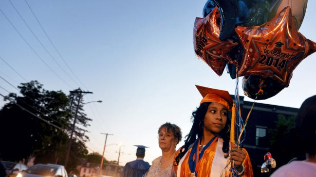 Q'ajaniyah Miller, 18, stands with her grandmother, Tina Maxfield, while waiting for her mother, Ronielle Kirkland, to pick them up after Miller graduated this month from William Penn Senior High School. Q'ajaniyah has twice been the victim of gun violence: Her father, Ajani Miller, died from a gunshot to the pelvis in 1999, and Miller was caught in crossfire outside her house last year. Her experiences have pushed her to study criminal justice this fall at Penn State.
