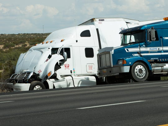 Kleine Motor Company provides an empty tractor-trailer, right, to carry cargo from a crashed RM Trucking unit on the side of Interstate 10 Tuesday, September 20, 2016.