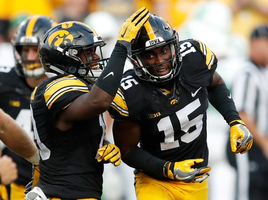 Iowa defensive back Josh Jackson (15) celebrates with teammate Miles Taylor, left, after intercepting a pass during the second half of an NCAA college football game against North Texas, Saturday, Sept. 16, 2017, in Iowa City, Iowa. (AP Photo/Charlie Neibergall)