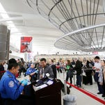 In this Oct. 30, 2014, file photo, a TSA officer, left, checks a passenger's ticket, boarding pass and passport as part of security screening at John F. Kennedy International Airport in New York.