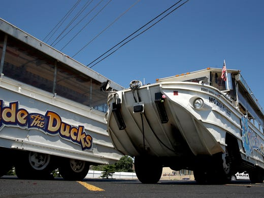 A man looks at an idled duck boat in the parking lot