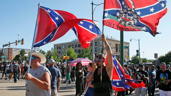 A group carries confederate flags past a Black Lives Matter rally in Oklahoma City, Sunday, July 10, 2016.