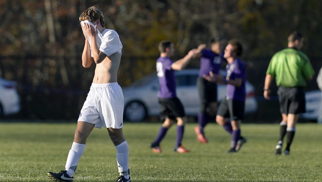 Fairport's Bobby Guilfoil walks off the field as New Rochelle players celebrate their state championship on Sunday in Middletown.