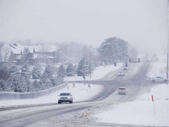 Traffic moves along Pacific Street near its intersection with 189th Street as snow falls in Omaha, Neb., Saturday, Jan. 12, 2019.