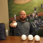Erik Cordier, pictured in his off-season home in De Pere, holds one of the balls he received in a Orix Buffaloes gift bag after signing with the Japanese team. On the wall behind Cordier is a large poster of the San Francisco Giants celebrating after winning the 2014 World Series. Cordier got to travel with the Giants during their playoff run that year and is pictured in the celebration.