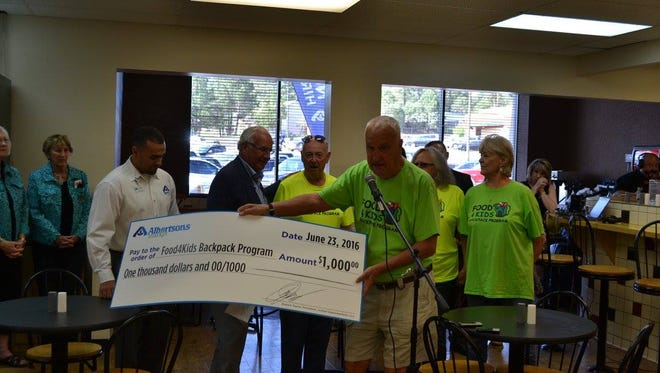 At its grand opening Friday, the staff of Albertsons Market of Ruidoso donated $1,000 to Ned Cantwell of the local Food4Kids backpack program to help feed area school children.