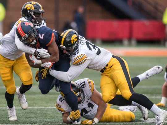 Illinois running back Reggie Corbin is tackled by Iowa's   Manny Rugamba, left, Brandon Snyder (37) and Bo Bower during a 28-0 Hawkeye win.