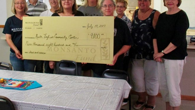 Williamsburg Monsanto employees Tammy Crossman and Bernard Connolly (far left) present a $9,800 grant award that funded a new range/oven and convection oven unit for the North English Community Center this summer. Also pictured from the Community Center are kitchen assistant Deb Grimm, director Jeanette Wells; board member Jen Rugg, head cook Sharon Barney, and additional Board Members Elaine Sorden, Jayne Garcia and Bonnie Romine.