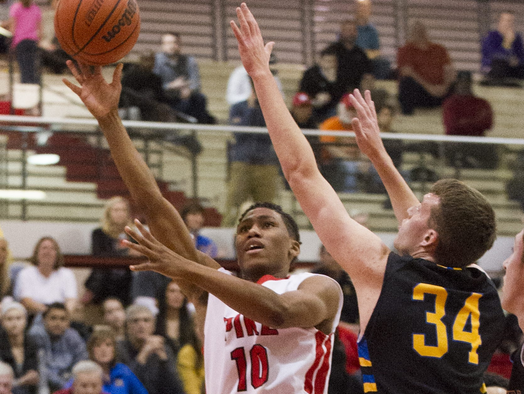 Pike High School sophomore Justin Roberts (10) puts up a shot around the defense of Carmel High School senior Keegan Culp (34) during the first half action. Pike High School hosted Carmel High School in MIC Conference boy's varsity basketball, Wednesday, Jan. 21, 2015.