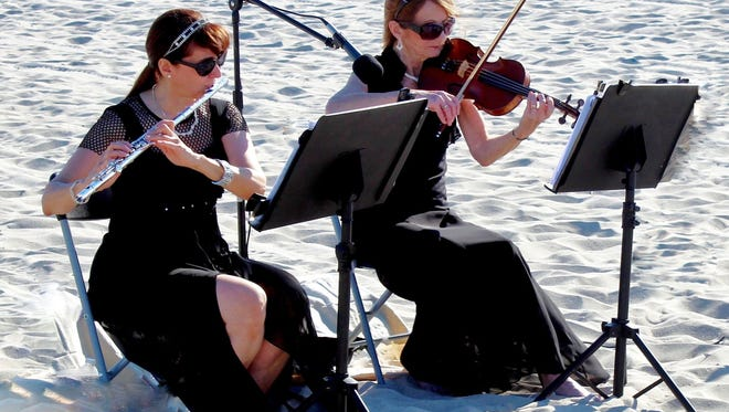 Michele Spadaro (left), Toms River, a flutist who owns Bridal Music, plays at a wedding on the beach in Ship Bottom with Winnie Burke, Farmingdale.