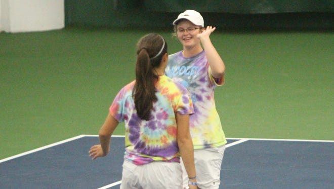 Emma Koppa greets teammate Annabelle Crowley after winning a point Oct. 13 at the state tennis meet in Madison.