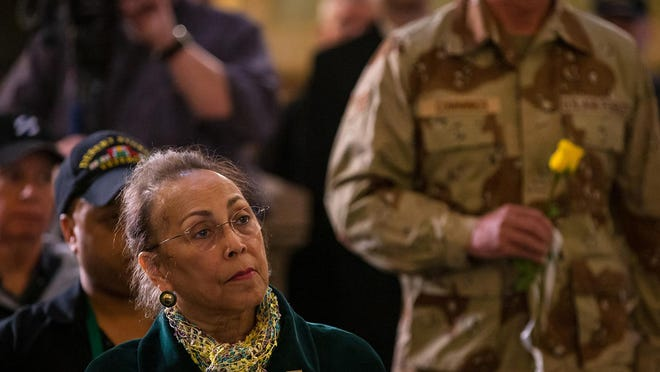 Phillipa Porter, the mother of Marine Lance Cpl. Christian Porter who was killed in Operation Desert Storm, watches as yellow roses are presented during a memorial service for the 18 service members from Illinois that lost their lives during Operations Desert Storm and Desert Shield during the 28th annual Desert Storm Remembrance Ceremony hosted by the Illinois Department of Veterans' Affairs at the state Capitol on Feb. 28, 2019, in Springfield.