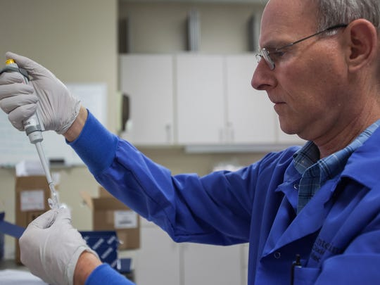 Medical Technologist Pat Bradley measures out a portion of DNA to be sent to a lab in this file photo.