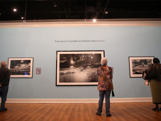 People examine the work photographer Clyde Butcher at the Museum of Florida History's temporary exhibit of his work entitled Preserving Eden, on Thursday, Feb. 9, 2017. The exhibit features large-format black and white landscape photographs.