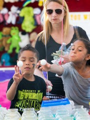 DANIEL R. PATMORE / SPECIAL TO THE GLEANER  Six year-old Kingston Collins (left) and nine year-old Jaela Eckles (right) pitch balls as Amanda Utley (center) watches at the Get Your Fish Here booth at the Tri-Fest in 2016.