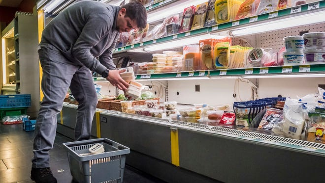 "A worker removes expired food in a local supermarket in Brussels on Monday, Jan. 16, 2017. The European Court of Auditors has chided the European Union's executive branch in a report, ""Combating Food Waste."""