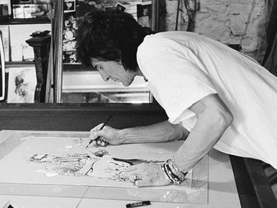Ronnie Wood of the Rolling Stones works on one of his drawings.