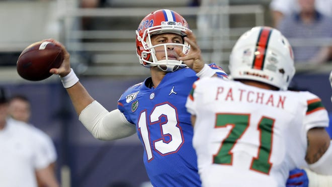 Florida quarterback Feleipe Franks (13) throws a pass as he is pressured by Miami defensive lineman Scott Patchan (71) during the first half of an NCAA college football game Saturday, Aug. 24, 2019, in Orlando, Fla.