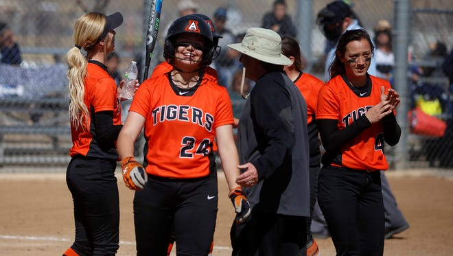 Aztec's Jocelyn Ulrich smiles while greeting teammates and coach Roy Johnson after hitting her third home run of the day during a game against Silver on Saturday at the Farmington Sports Complex.