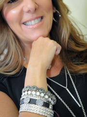 Laura D'Urso, who sells Touchstone Crystal by Swarovski jewelry, displays a Wrist Party, which is a variety of crystal bracelets.