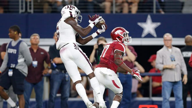 Texas A&M Aggies defensive backl Donovan Wilson (6) intercepts the ball in the second quarter against Arkansas Razorbacks receiver Jojo Robinson (17) at AT&T Stadium.