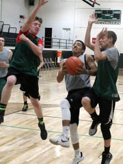 River O'Connor, far left, and Tyson Hughes, far right, attempt to stop Joe Montoya from scoring during practice Monday evening.