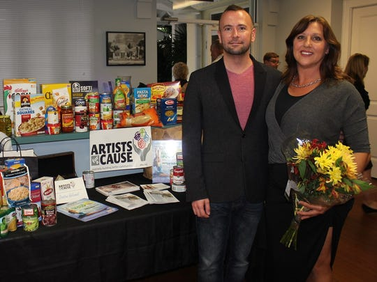 Artists for a Cause founder Terry Barber stands with Dance for Food director Anna Preston in front of food raised at a Dance for Food event.