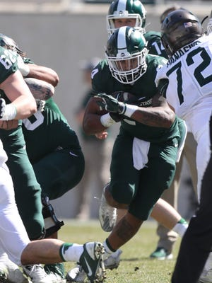 Michigan State running back Gerald Holmes runs the ball during the spring game at Spartan Stadium, Saturday, April 1, 2017.