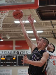 Lexington's Cade Stover goes for a layup as Mansfield Senior's David Hall closes in.
