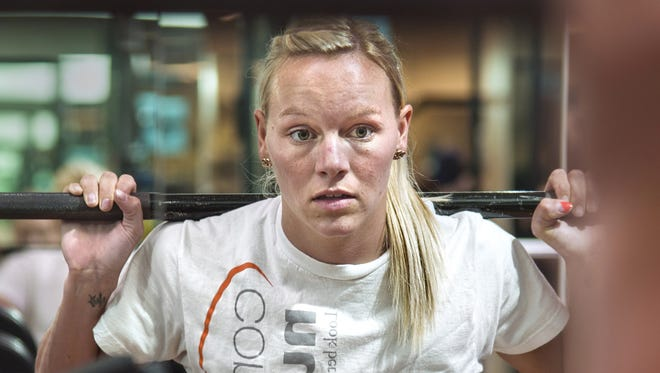 U.S. short track speed skater Emily Scott watches herself in the mirror as she lifts more than 170 pounds during a workout in June.