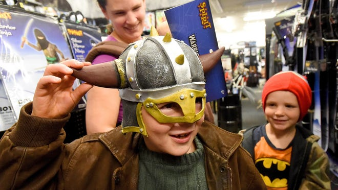 Seven-year-old Elijah Rutherford of Nelson County tries on a costume helmet with mother Kate Rutherford and brother Lee Rutherford, 5, behind him. They shop at the Spirit Halloween store at Willow Oak Plaza shopping center in Waynesboro on Thursday, Oct. 22, 2015.