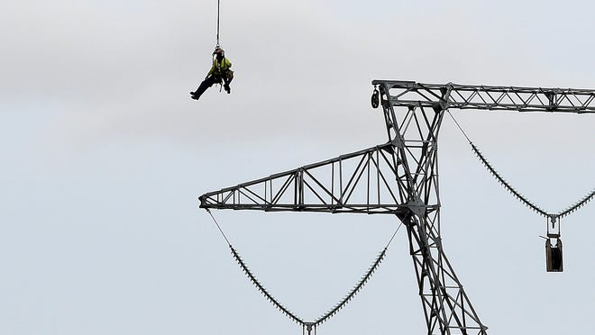 A helicopter ferries workers suspended on a cable from one new Dominion Virginia Power transmission line tower to another as they check the insulators and other components before the cables can be strung in Fishersville on Wednesday, Nov. 18, 2015.