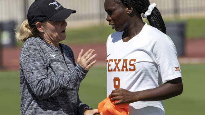 """Texas head soccer coach Angela Kelly speaks with Teni Akindoju during a match against Grambling in the 2019 season. Prior to kickoff between Texas and Oklahoma last Friday, Akindoju and every Longhorns player had a social justice poster in hand with messages such as """"End Racism"""" and """"The time for a change is NOW."""""""