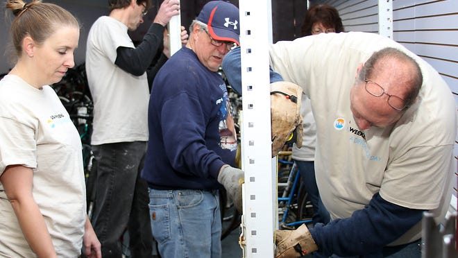 """The staff of the Oshkosh Northwestern volunteered their help at the Community Bike Program for """"Make A Difference Day"""" on Saturday. They helped in the construction of shelves to better hold the bike parts they use to repair broken bikes."""