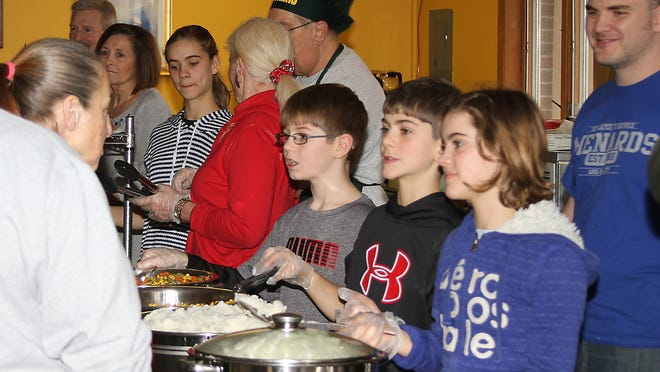 Hayden Metzger, Oscar Pollard, and Drew Pollard serve up mashed potatoes and vegetables at the Christmas meal at Father Carr's Place 2B for those in need in keeping with Father Carr's mission to help the heeding.