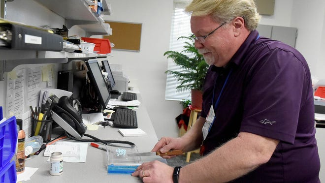 Pharmacy manager Curtis Shinaberry counts out medication in the pharmacy at Valley Community Services Board in Staunton on Friday, Jan. 2, 2015.