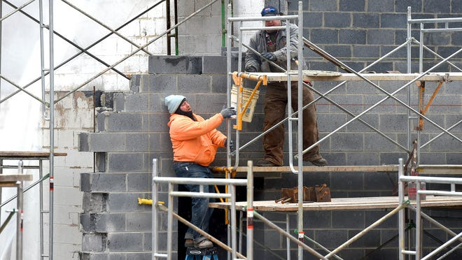 A bucket is passed from one worker to another as work continues to renovate the Wayne Theatre in Waynesboro on Thursday, Jan. 29, 2015.