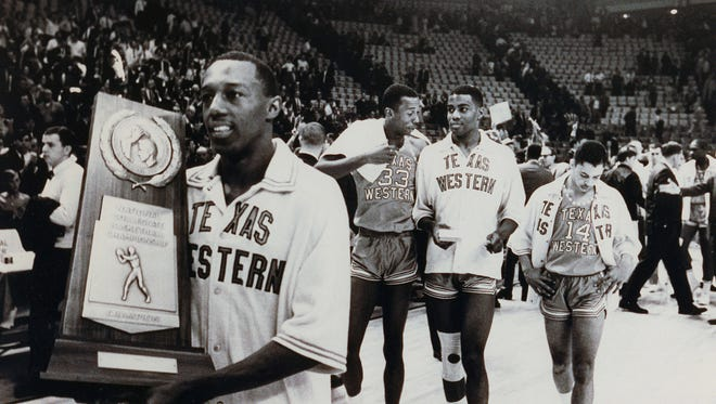Members of the 1966 NCAA Championship team walk off the court with the NCAA trophy.