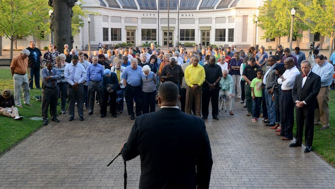 Dr. Darryl Coleman, Pastor of Mother Liberty CME Church leads a prayer during a community prayer sponsored by Historic First Baptist Church and First Baptist Church in Jackson, Wednesday evening at the Madison County Courthouse.