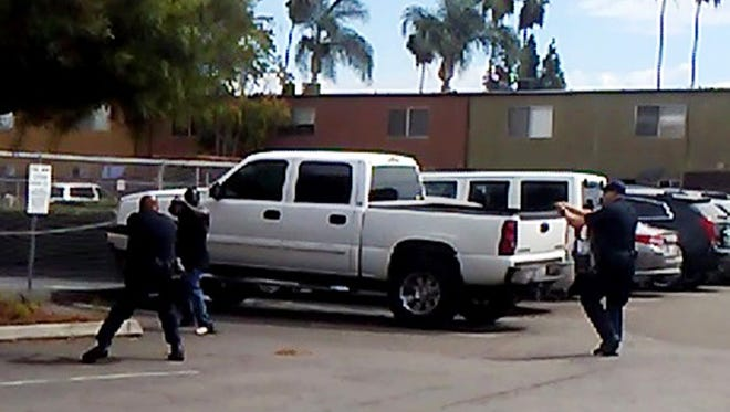 """In this Tuesday, Sept. 27, 2016 frame from video provided by the El Cajon Police Department, a man, second from left, faces police officers in El Cajon, Calif. The man reportedly acting erratically at a strip mall in suburban San Diego was shot and killed by police after pulling an object from his pocket, pointing it at officers and assuming a """"shooting stance,"""" authorities said. Some protesters claimed the man was shot with his hands raised, but police disputed that and produced the frame from cellphone video taken by a witness that appeared to show the man in the """"shooting stance"""" as two officers approached with weapons drawn."""