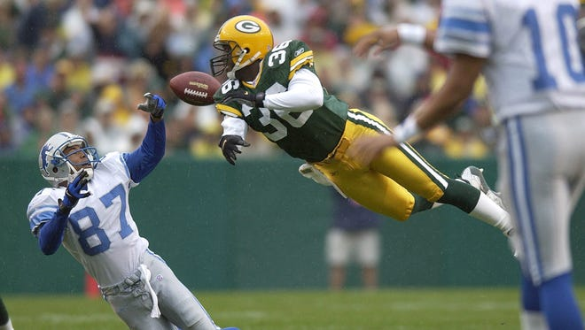 Green Bay Packers Leroy Butler knocks the ball away from Lions receiver Johnnie Morton during  a game at Lambeau Field on Sept. 9, 2001.